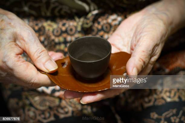 Old hands holding asian tea