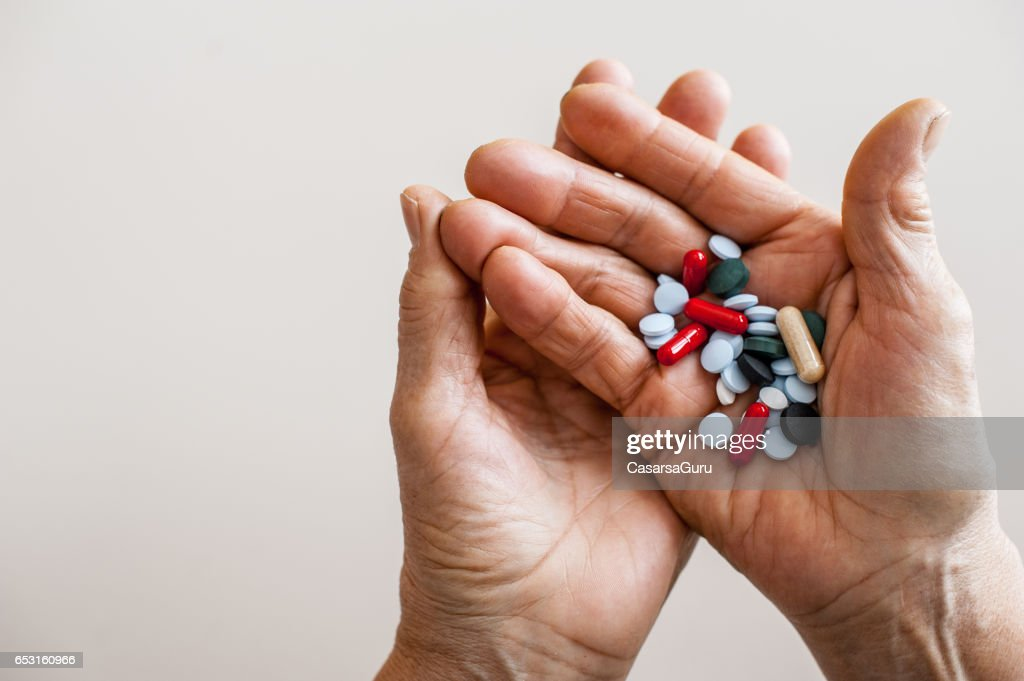 Old Hands Taking Medicine - Close Up : Stock Photo