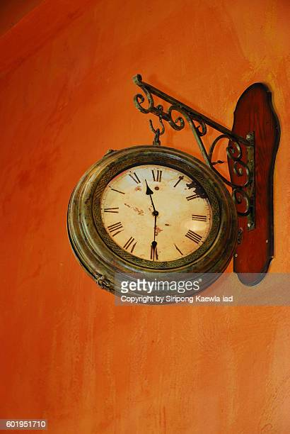 Old hanging clock on the orange wall