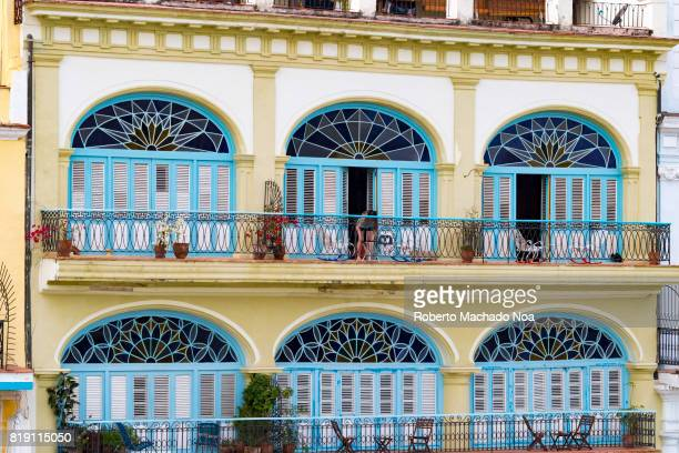 Old Havana colonial architecture Balconies of a colonial building with floral stained glass design on arches and blue and white wooden louvered doors