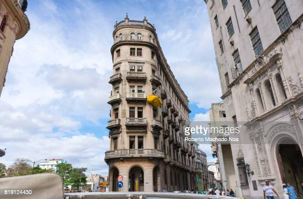 Old Havana flatiron building Wide view of beige gothic building taken from a car with clouds forming patterns in the background sky