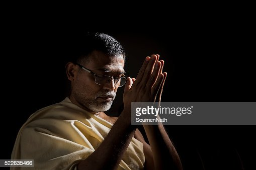 Old Hindu man praying with folded hands