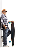 Full length portrait of an old hipster with a longboard leaning against a wall isolated on white background