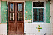 Locked wooden front door and window of traditional chinese old house in Georgetown, Penang. Vintage effect