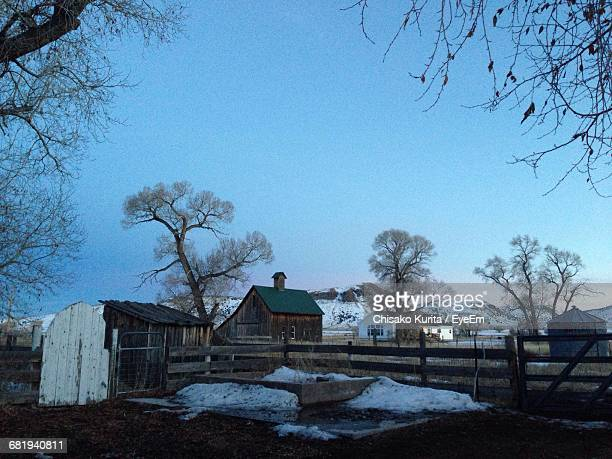 Old Houses And Bare Trees On Field Against Sky During Winter