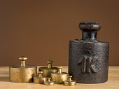 Old iron 1kg weight and smaller brass weights for a kitchen scale standing on a table