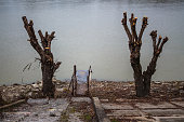 Old iron pier by the river between two felled trees. Overcast weather