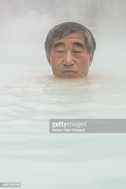 Old Japanese man enjoying onsen a natural hot spring bath in the middle of winter in the mountains surrounding Akita Japan It's snowing and the only...