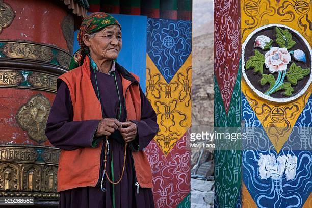 Old Ladakhi woman comes to turn the giant Buddhist prayer wheel near Hunder monastery in Nubra valley Ladakh Jammu and Kashmir India