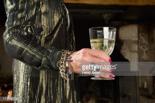 Old ladies hand with glass of wine