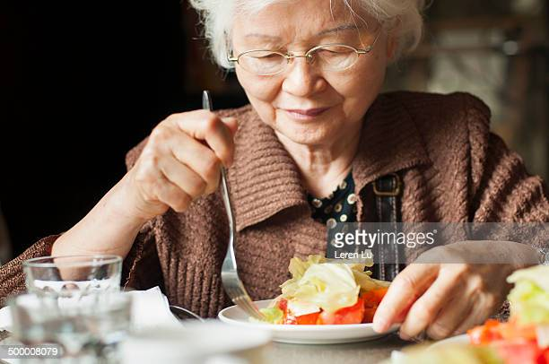 Old lady eating salad gracefully