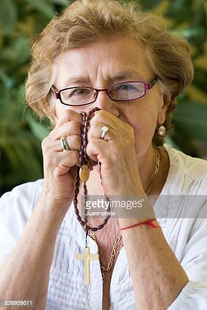 Old lady prier avec son du Rosaire