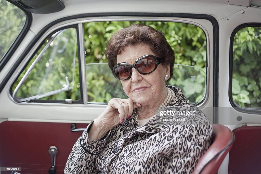 Old lady sitting inside an old car : Stock Photo