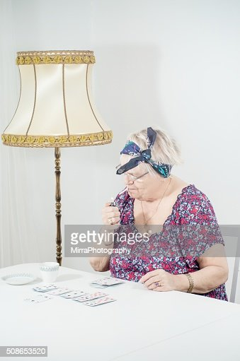 Old lady smoking and playing with cards : Stock Photo