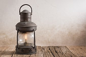 old kerosene lantern on old wood with grunge wall