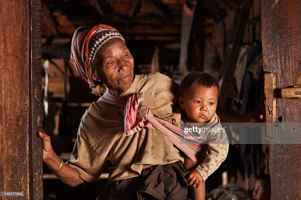 Old Lao woman holding a baby in Northern Laos : Stock Photo