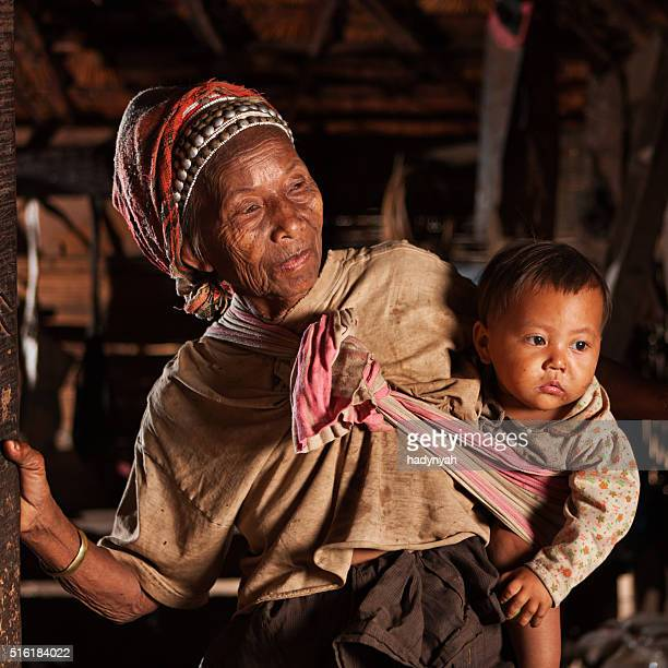 Old Lao woman holding a baby in Northern Laos