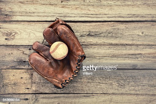 Old leather baseball mitt and ball on grunge wood background : Stock Photo