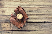 Vintage leather baseball mitt and ball on grunge wood background