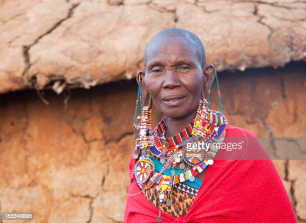 Old maasai woman with traditional jewellery in front of hut
