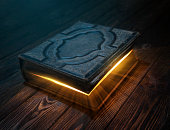 Old magic book on wooden table with light rays coming out form instide