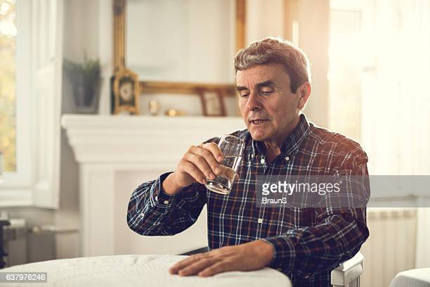 Old man about to drink glass of fresh water.