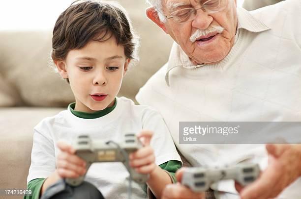 Vecchio uomo e sua nipote giocare videogiochi a casa