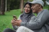 portrait of old man and woman using mobile phone while relaxing together in the park