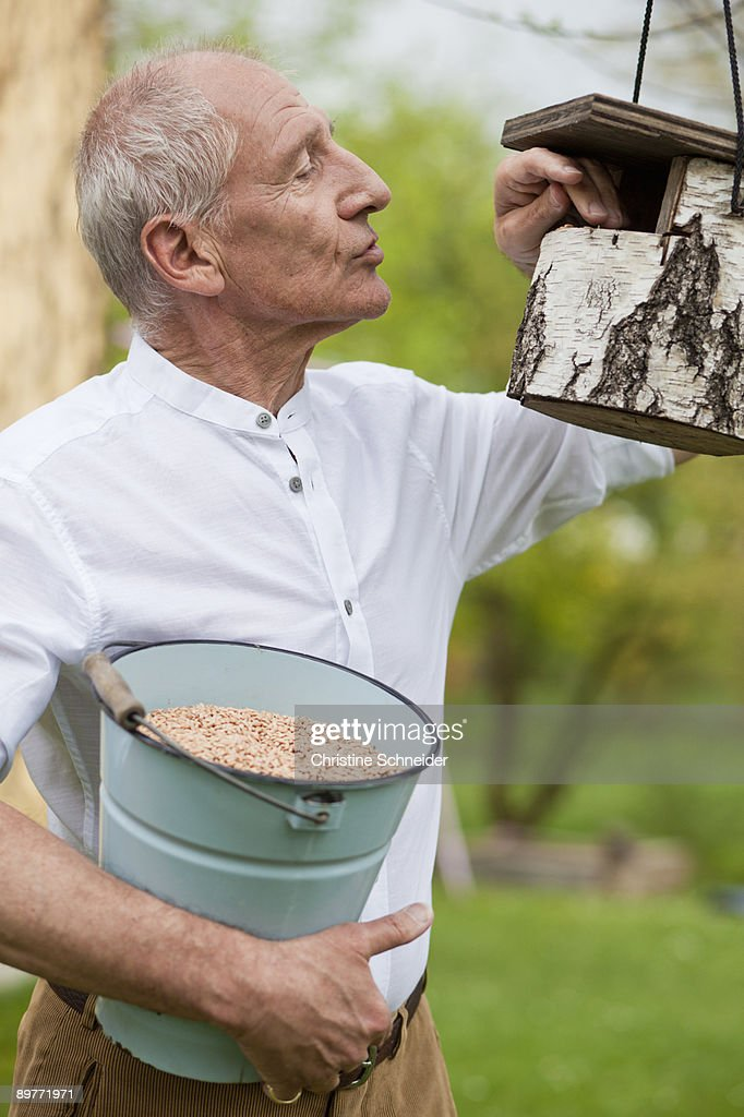 old man filling up bird house