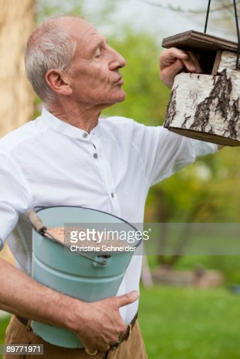 old man filling up bird house : Stock Photo