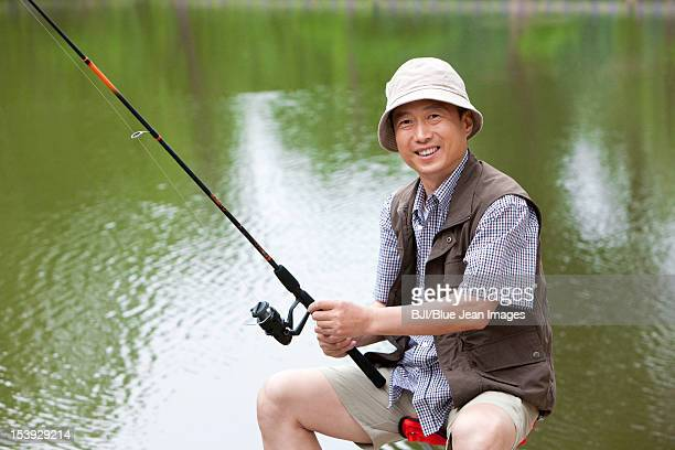 Old man fishing by a pond