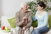 Old man holding a cane and smiling to young woman