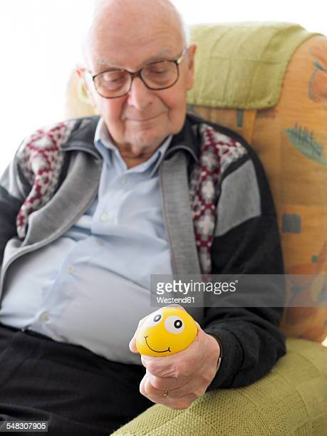 Old man in armchair squeezing stress ball