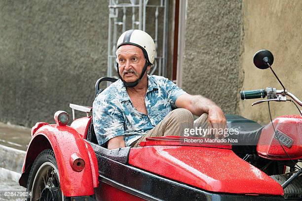 Old man in printed shirt sitting in a rain soaked red side car of a bike Waiting for the journey to begin