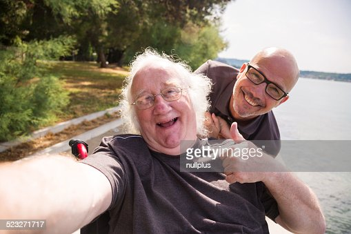 old man in wheelchair taking a selfie with his phone