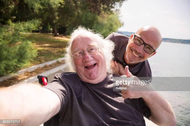Alter Mann im Rollstuhl, die ein selfie mit seinem Smartphone