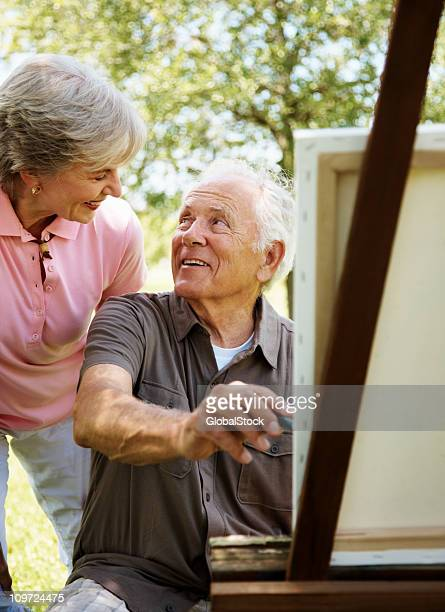 Old man painting a picture on canvas with his wife
