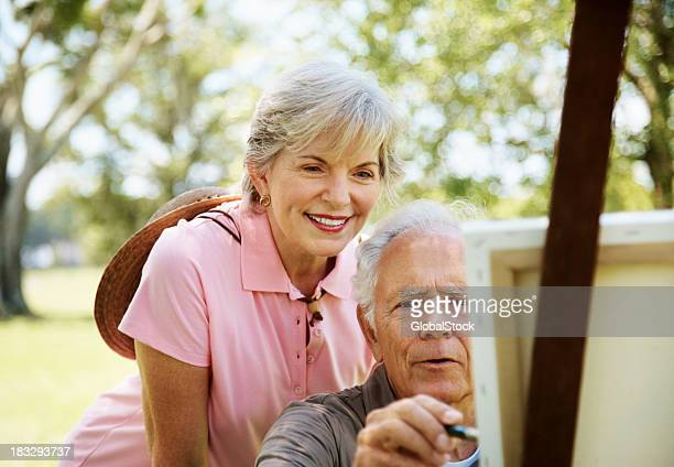 Old man painting on canvas with his wife