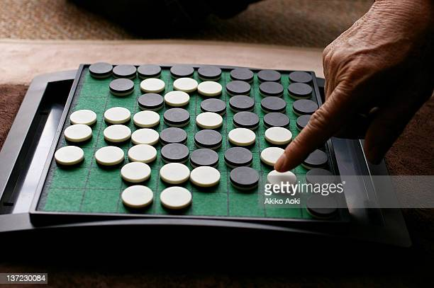 Old man playing Othello game