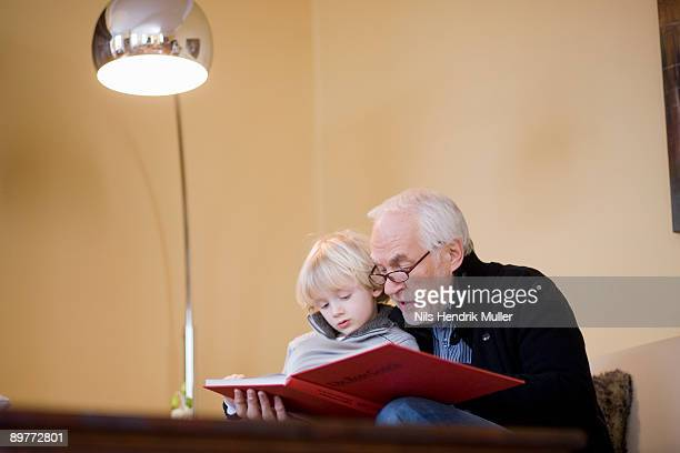 old man reading book to young boy