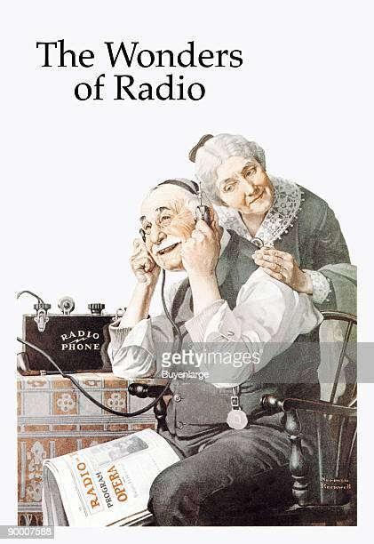 Old Man senior citizen listens to the wonders of radio on a headset while his wife leans on his back trying to hear He has Radio Newspaper on his knee
