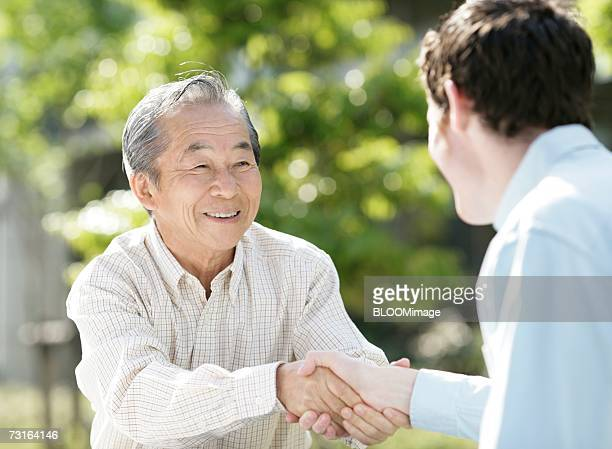 Old man shaking hands with young man