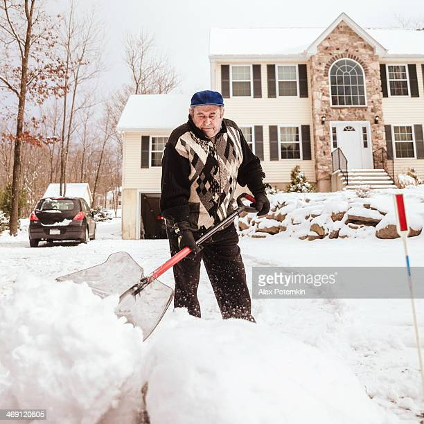 Old man shoveling a path in the snow