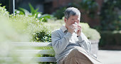 old man sick and sneeze with tissue paper outdoor