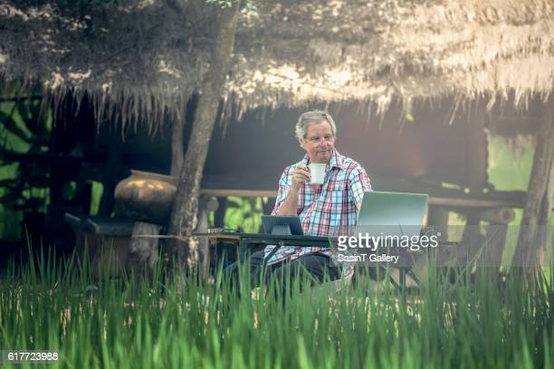 Old man sitting at a desk on a outdoor
