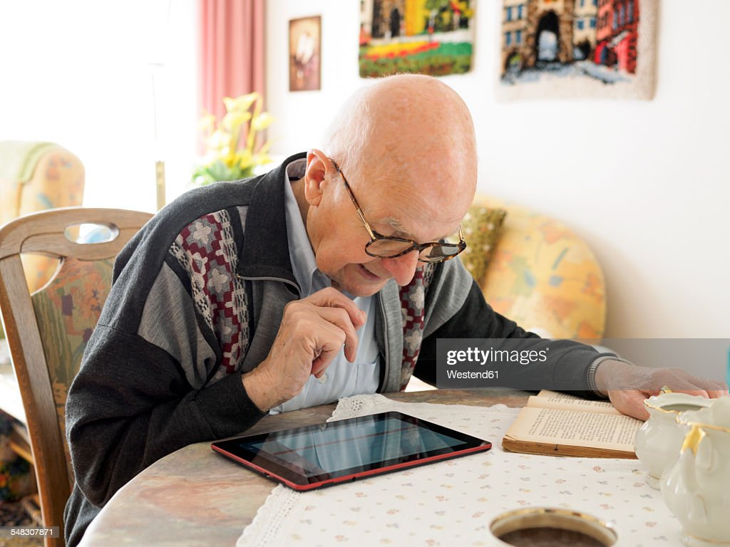 Old man sitting at table using digital tablet