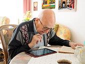 Old man sitting at table using digital tablet