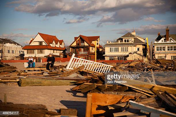 Old man sitting next to ruined homes after Sandy hurrican