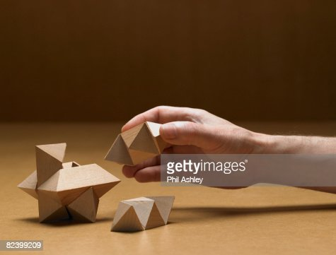 old man solving a wooden puzzle : Stock Photo