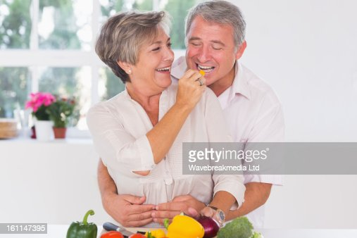 Old man tasting vegetable held by wife : Stock Photo